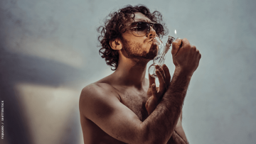 a shirtless man smoking weed through a bong