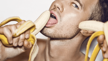 a man with bananas near his mouth and face