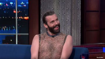Johnathan Van Ness wearing a sparkly shirt, skirt, heels on Colbert set